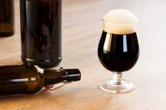 玻璃棕色啤酒,在桌上 库存照片