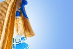 玻璃清洁剂浪花瓶和布料有蓝色背景 库存图片