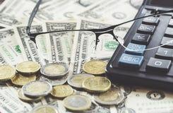 玻璃特写镜头在美元钞票的与硬币和计算器 到达天空的企业概念金黄回归键所有权 图库摄影