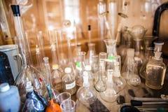 玻璃瓶、试管、烧瓶和杯子在一个老化工实验室 库存照片