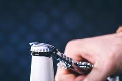 玻璃瓶啤酒和开启者在黑暗的背景 打开瓶的手 酒精和饮料概念 图库摄影