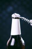 玻璃瓶啤酒和开启者在黑暗的背景 打开瓶的手 酒精和饮料概念 库存照片