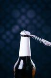 玻璃瓶啤酒和开启者在黑暗的背景 打开瓶的手 酒精和饮料概念 免版税库存照片