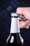 玻璃瓶啤酒和开启者在黑暗的背景 打开瓶的手 酒精和饮料概念 免版税库存图片
