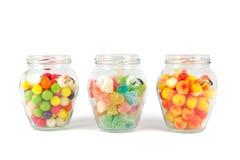 玻璃瓶子充满不同的五颜六色的糖果 免版税库存图片
