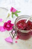 玻璃瓶子和一点匙子有茶玫瑰花瓣的在轻的大理石背景阻塞 复制文本的空间 免版税库存照片