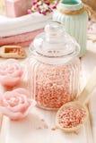 玻璃瓶子在白色木桌上的桃红色海盐 免版税图库摄影