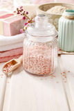 玻璃瓶子在白色木桌上的桃红色海盐 库存图片