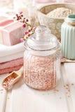 玻璃瓶子在白色木桌上的桃红色海盐 库存照片
