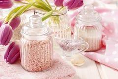 玻璃瓶子在白色木桌上的桃红色海盐 免版税库存图片