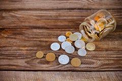 从玻璃瓶子溢出的硬币 库存图片