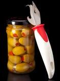 玻璃瓶子用罐子橄榄和一把开罐头用具在黑背景 图库摄影