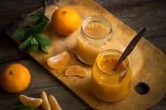 玻璃瓶子用自然婴儿食品用在木t的蜜桔 免版税库存照片