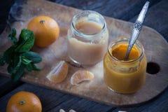 玻璃瓶子用自然婴儿食品用在木t的蜜桔 免版税库存图片