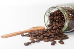 从玻璃瓶子的溢出的咖啡豆 图库摄影