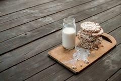 玻璃瓶子自创牛奶,在木背景桌上的可口薄脆饼干 免版税图库摄影