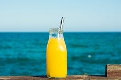 玻璃瓶用与秸杆的柑桔汁橙色蜜桔在木路轨、绿松石海和蓝天在背景中 库存照片