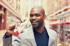 从玻璃瓶的年轻微笑的人饮用的苏打 免版税库存图片