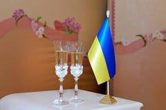 玻璃用乌克兰的香槟和旗子 库存图片