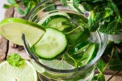 玻璃用刷新的戒毒所黄瓜水用新鲜薄荷和石灰在谷仓木箱子、成份、春天或者夏天 库存照片