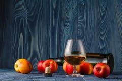玻璃用卡尔瓦多斯白兰地酒和黄色苹果在一张木桌上 免版税库存照片