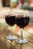 玻璃用在一张桌上的红葡萄酒在一个室外咖啡馆有一被弄脏的背景和bokeh 免版税图库摄影