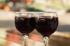 玻璃用在一张桌上的红葡萄酒在一个室外咖啡馆有被弄脏的背景 库存照片