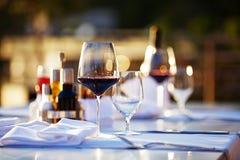 玻璃用在日落的红葡萄酒 库存照片