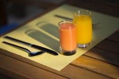 玻璃用新鲜的汁液在早餐桌上服务 库存照片