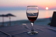 玻璃用红葡萄酒和日落在海滩在背景 夏令时假期概念 免版税图库摄影