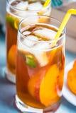 玻璃用自创冰茶,调味的桃子 新近地削减安排的桃子切片 浅兰的木背景 免版税图库摄影