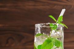 玻璃用酒精饮料填装了从水多的石灰、兰姆酒、新鲜薄荷和冰块在黑暗的木背景 复制空间 免版税库存照片