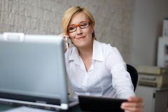 玻璃电话的白肤金发的女实业家由智能手机 库存图片