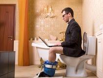 玻璃的人与膝上型计算机坐马桶 免版税图库摄影