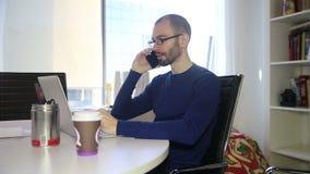 玻璃的人谈电话和工作膝上型计算机的 股票视频