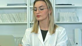玻璃的可爱的女性医生使用坐在总台的膝上型计算机 免版税库存照片