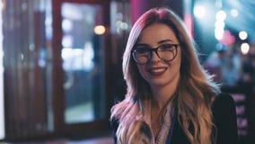 玻璃的可爱的白肤金发的妇女与红色唇膏,在站立在夜城市的时髦成套装备,转向照相机和 影视素材