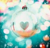 从玻璃的垂悬的圣诞节球与在蓝色bokeh背景的心脏标志与雪 库存照片