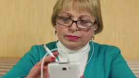 玻璃的妇女与抽香烟的白色智能手机 股票录像