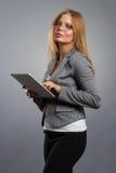 玻璃的少妇与片剂在灰色背景的计算机个人计算机 图库摄影