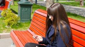 玻璃的少妇在城市公园使用细胞智能手机 女孩坐一条红色长凳室外在春天和用途a 股票视频