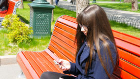 玻璃的少妇在城市公园使用细胞智能手机 女孩坐一条红色长凳室外在春天和用途a 免版税图库摄影