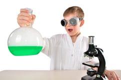 黑玻璃的惊奇的科学家男孩在他的手上拿着一个烧瓶 库存图片