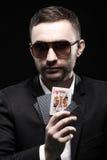 黑玻璃的打牌者,在有开放一张卡片的一个赌博娱乐场在黑背景 免版税库存图片