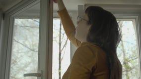 玻璃的浅黑肤色的男人在一个晴朗的春日洗涤窗口 影视素材