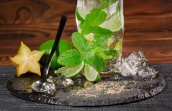 玻璃的特写镜头用酒精饮料填装了从水多的石灰、兰姆酒、新鲜薄荷和冰在黑暗的背景 复制空间 免版税库存照片