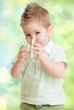 从玻璃的男孩饮用水 免版税库存图片