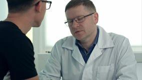 玻璃的男性医生咨询男性患者的 股票录像