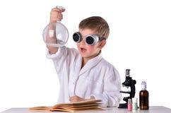 黑玻璃的科学家男孩在他的手上拿着一个空的烧瓶 库存图片