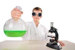 黑玻璃的科学家男孩拿着大烧瓶fith绿色起泡沫的流体 免版税图库摄影